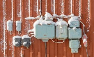 Retro style of electric circuits, sockets and junction boxes mounted on a red wooden wall. Some snow on the wall